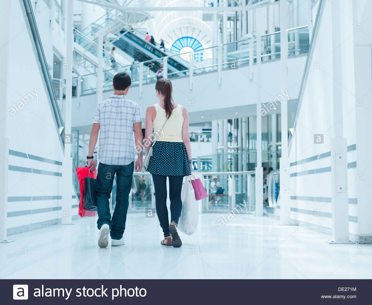 Couple carrying shopping bags in mall - Stock Image