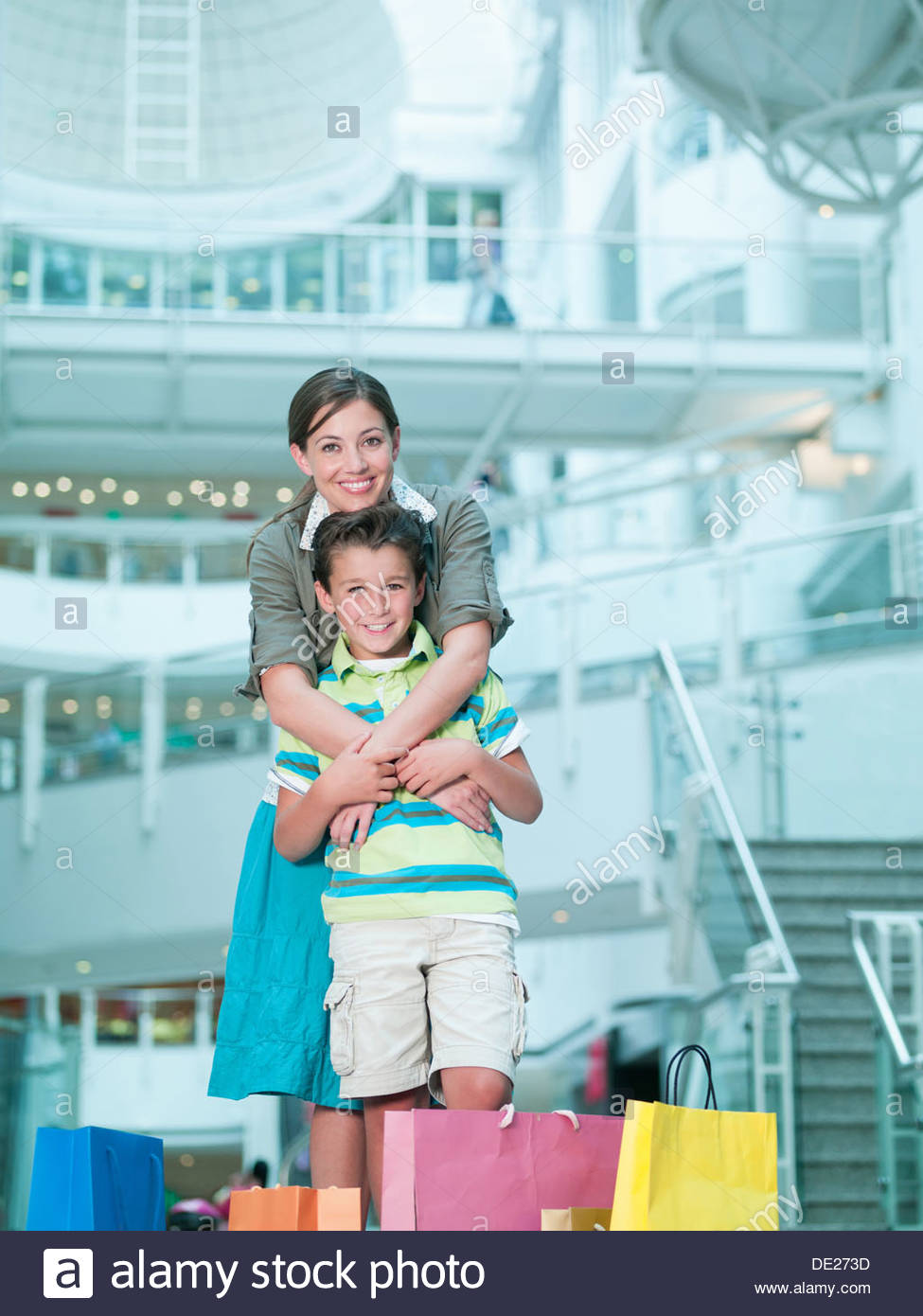 Mother hugging son in shopping mall - Stock Image