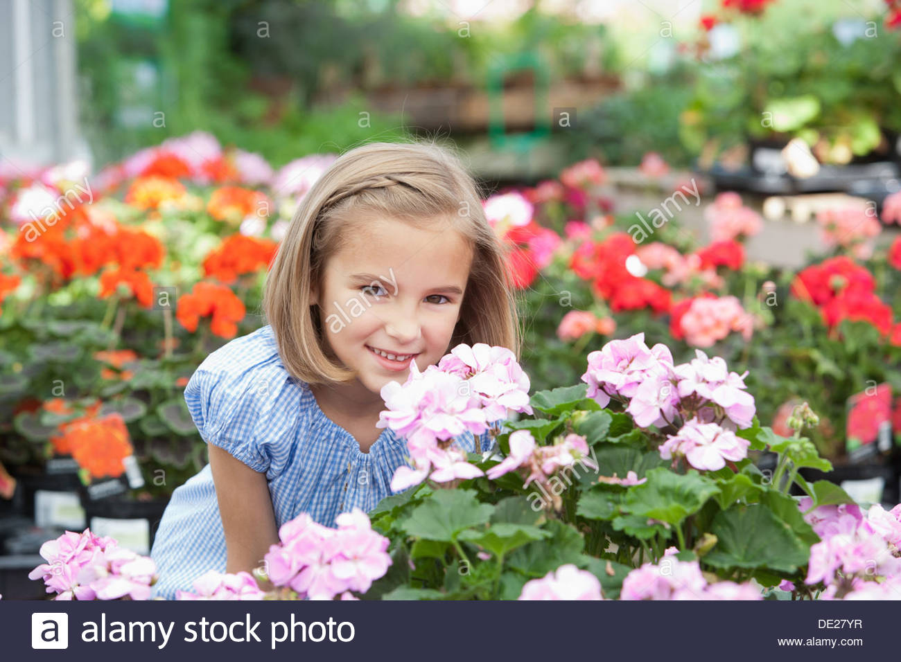 Girl smelling flowers at nursery - Stock Image