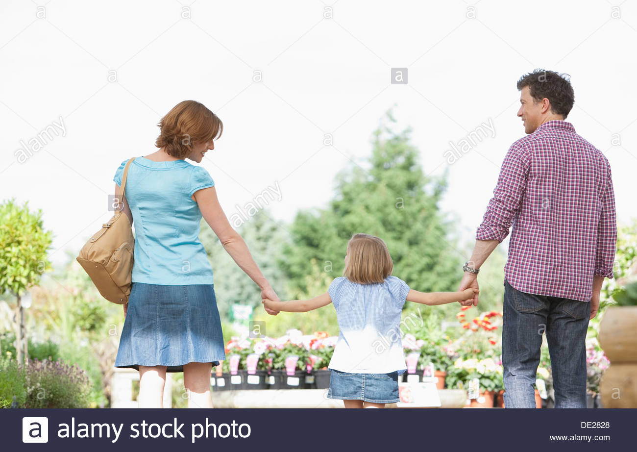 Parents holding hand daughter in nursery - Stock Image