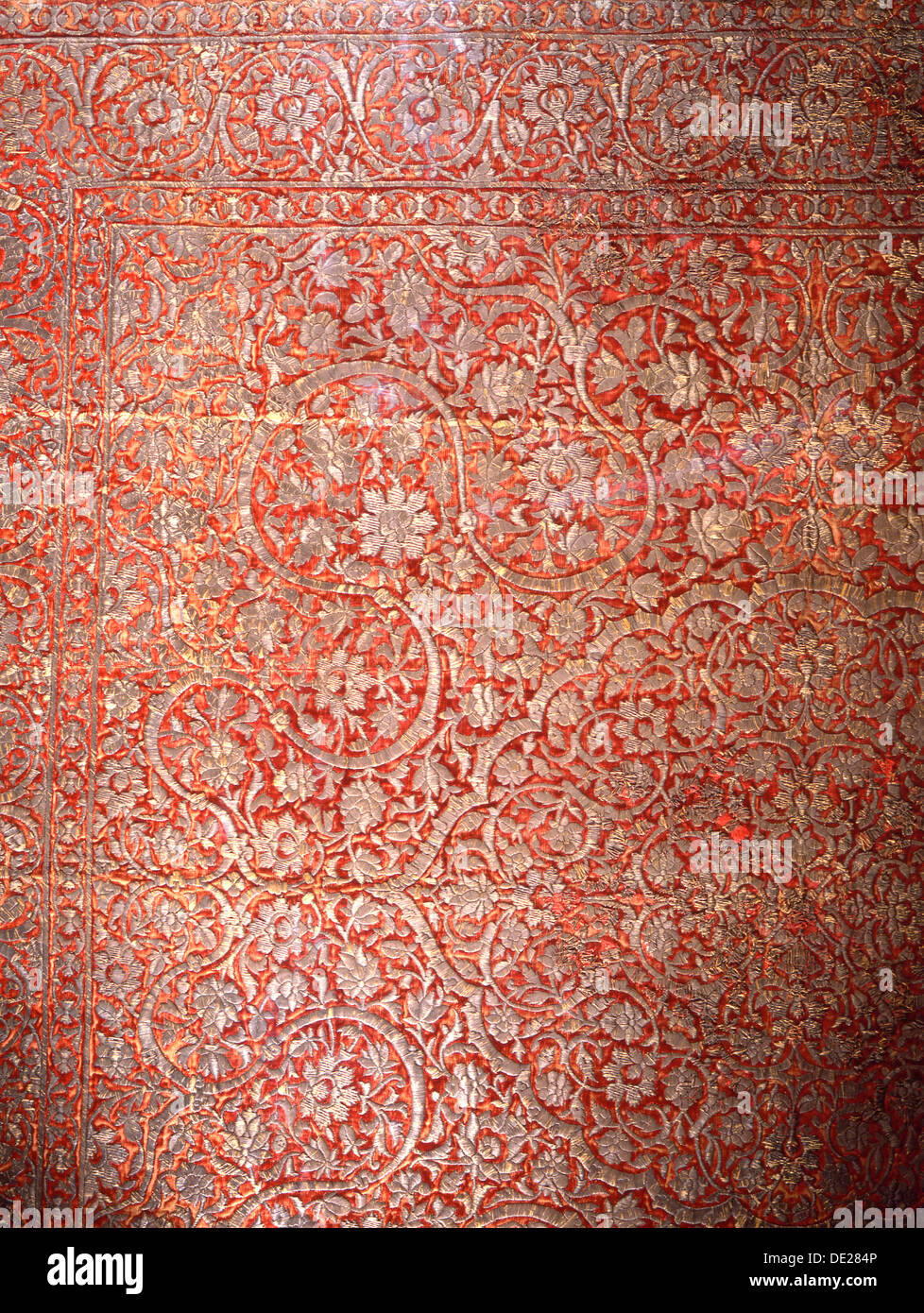 Red silk carpet with heavy silver arabesque designs. - Stock Image