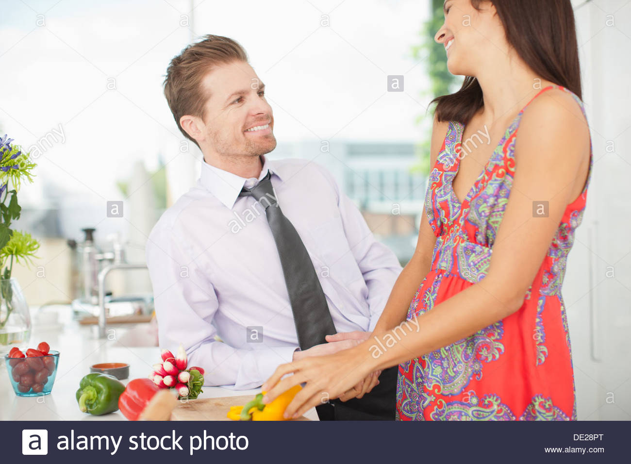 Husband talking to wife while she cuts vegetables in kitchen - Stock Image