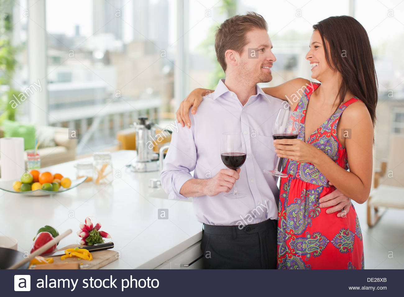 Couple drinking red wine in kitchen - Stock Image