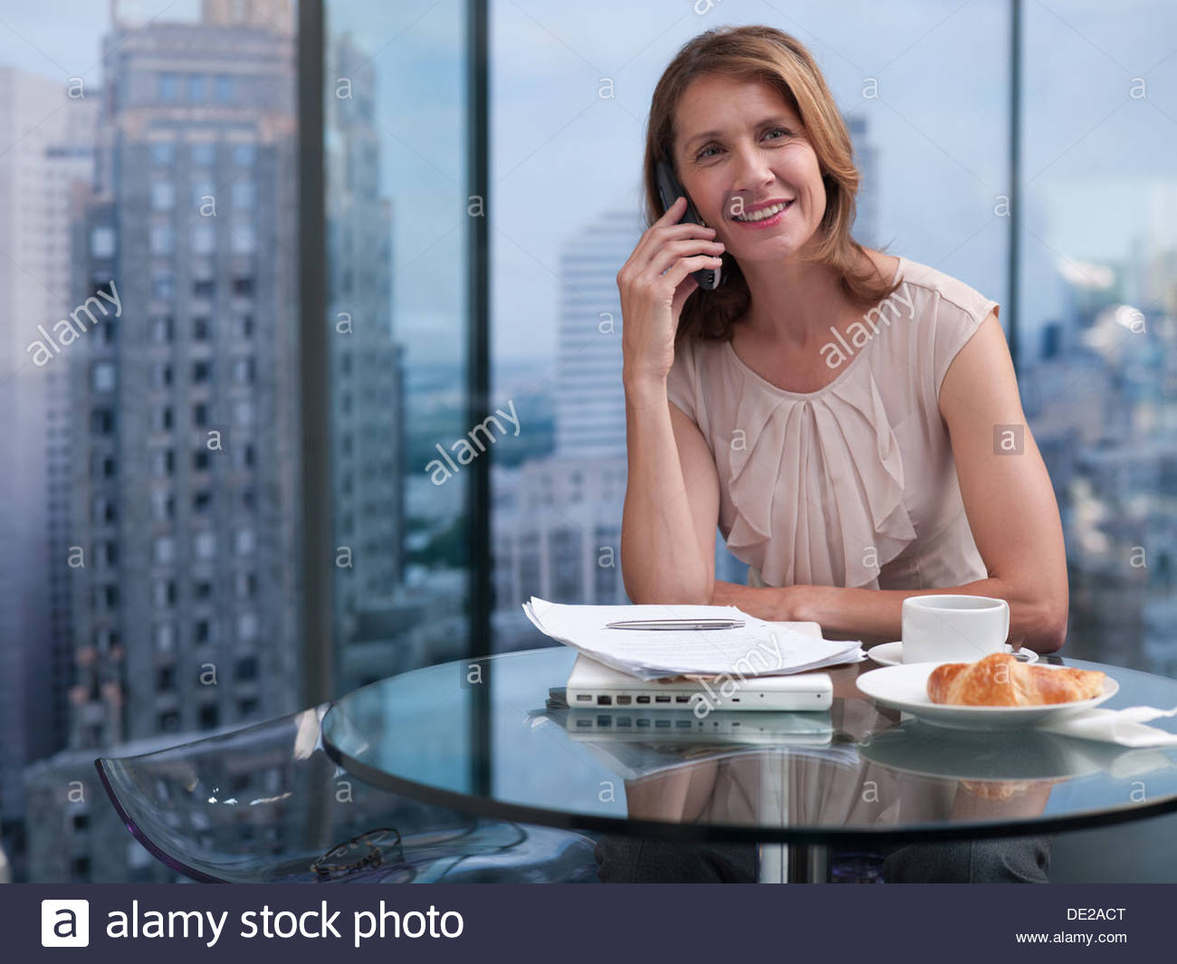 Woman talking on telephone with cityscape in background - Stock Image