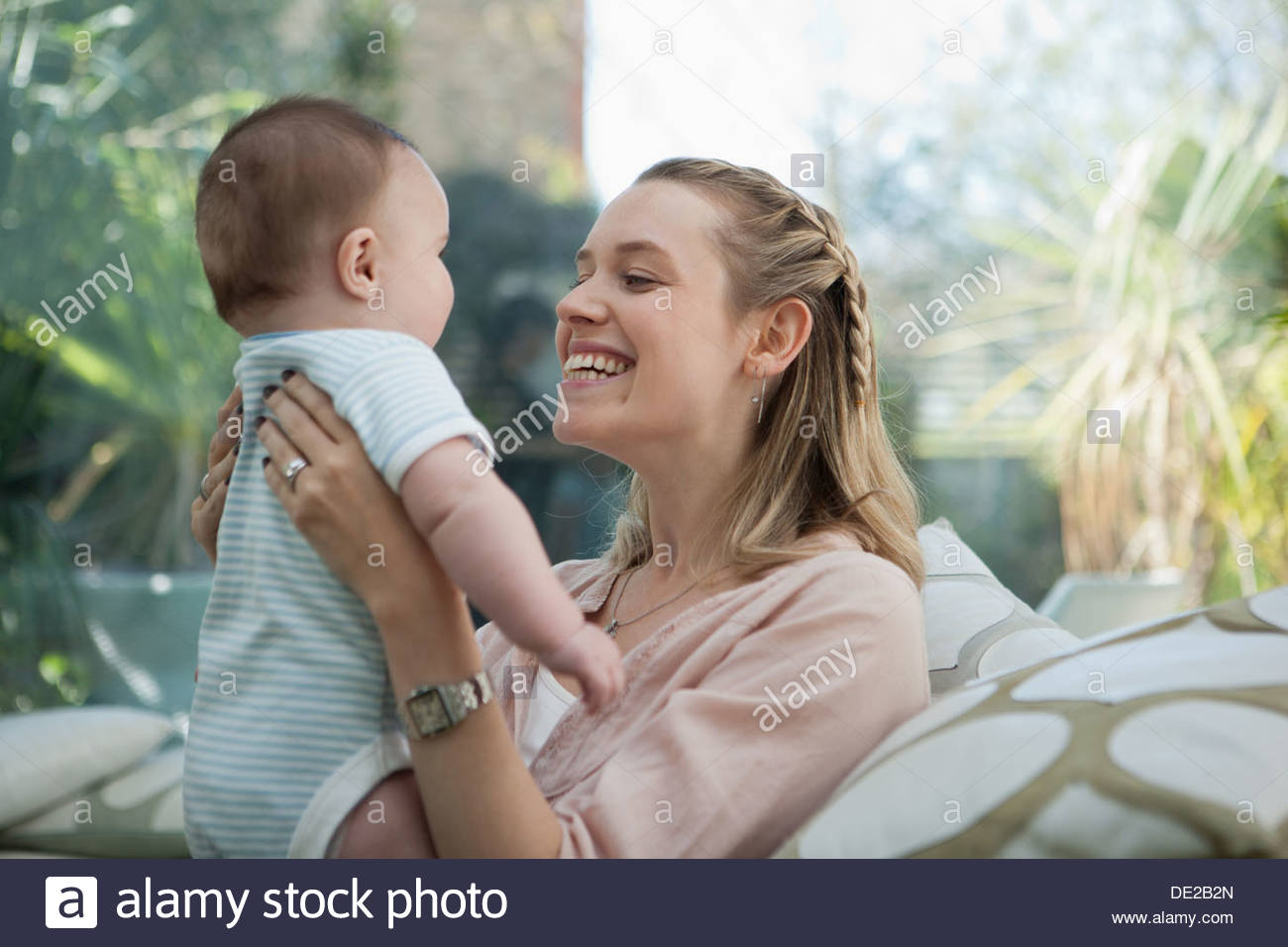 Smiling mother lifting baby son - Stock Image