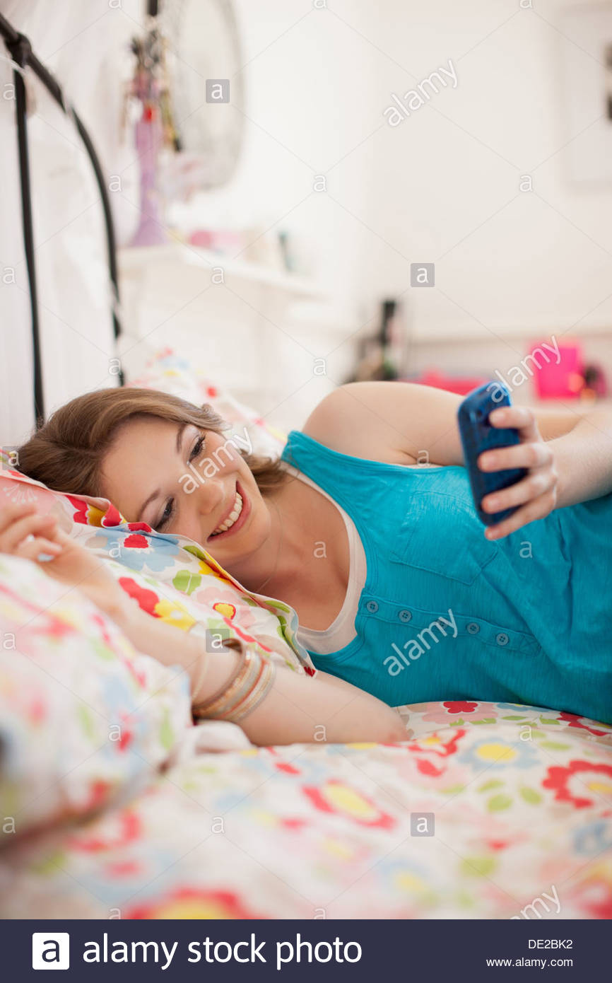 Smiling teenage girl text messaging on cell phone in bedroom - Stock Image