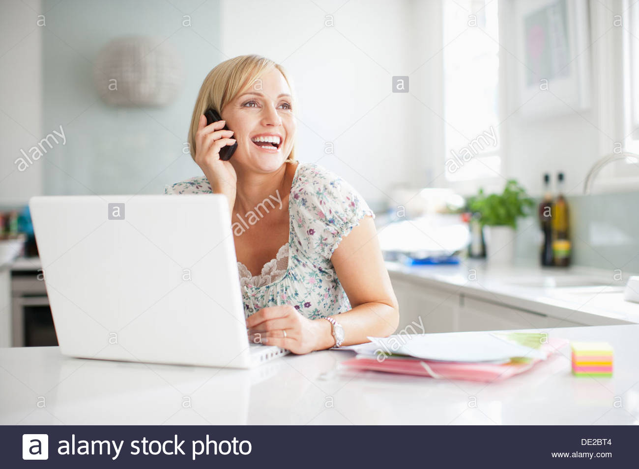 Woman using laptop and talking on cell phone - Stock Image