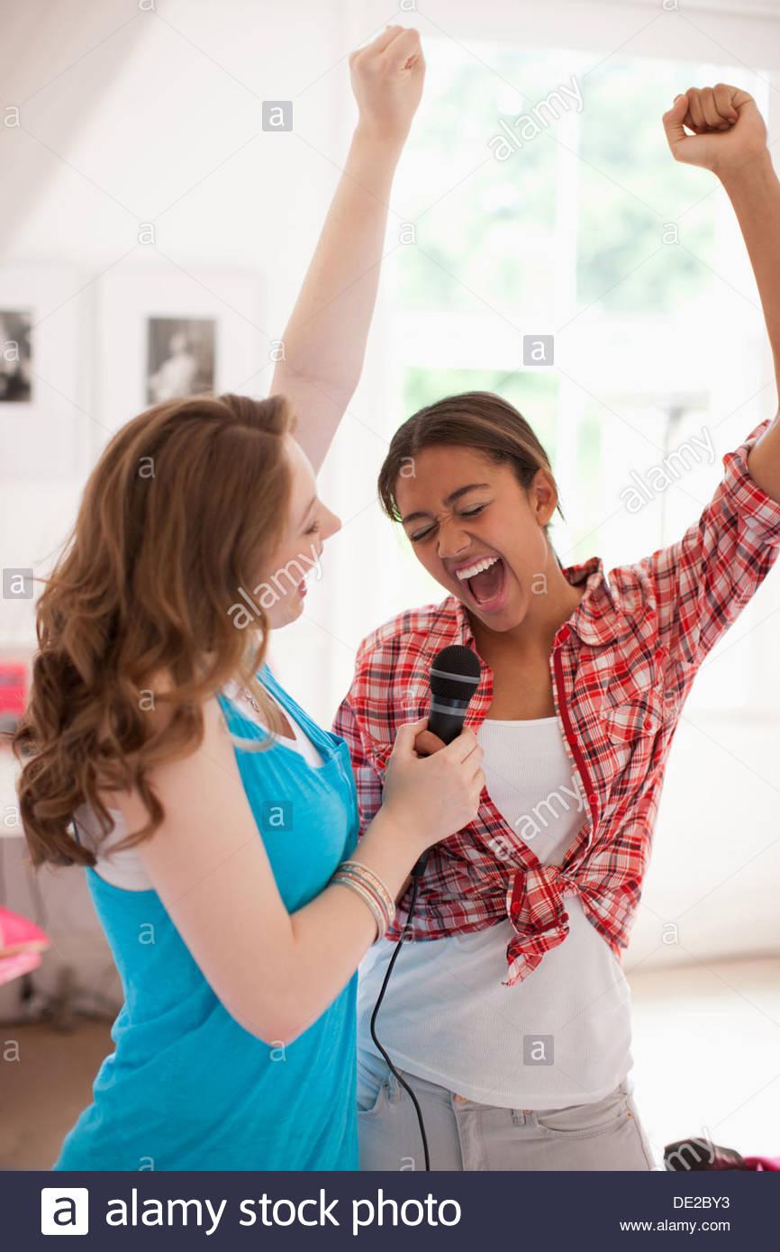 Teenage girls singing into microphone Stock Photo