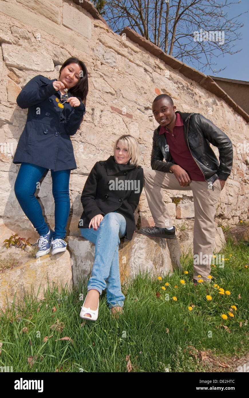 Young Asian woman, European woman and coloured young man standing by a wall - Stock Image