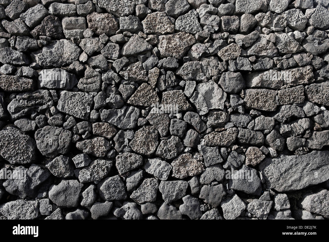 Dry wall constructed from individually stacked lava rocks, typical feature of Lanzarote, Lanzarote, Canary Islands, Spain - Stock Image