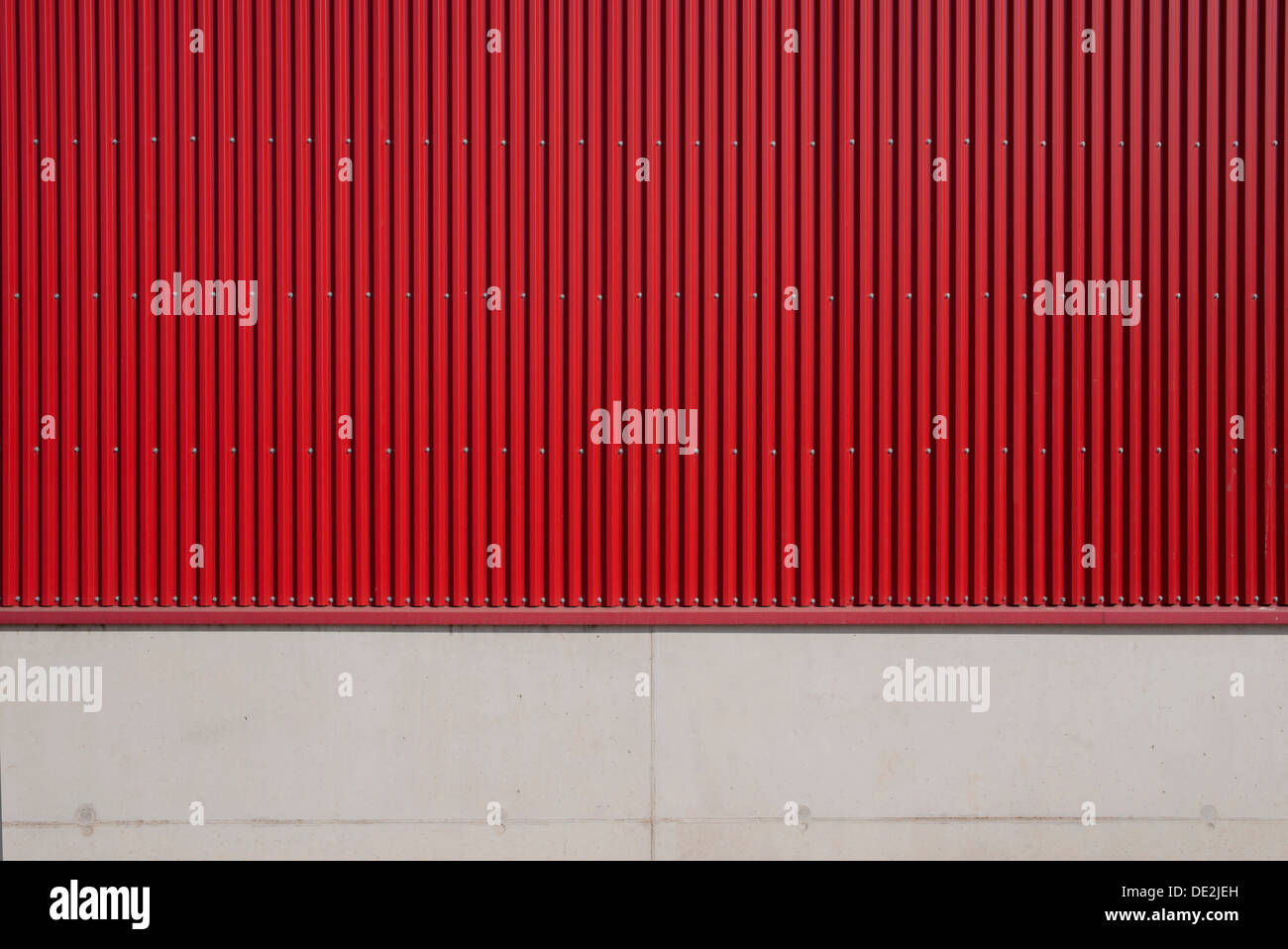 Wall of a factory building with red corrugated iron and concrete - Stock Image