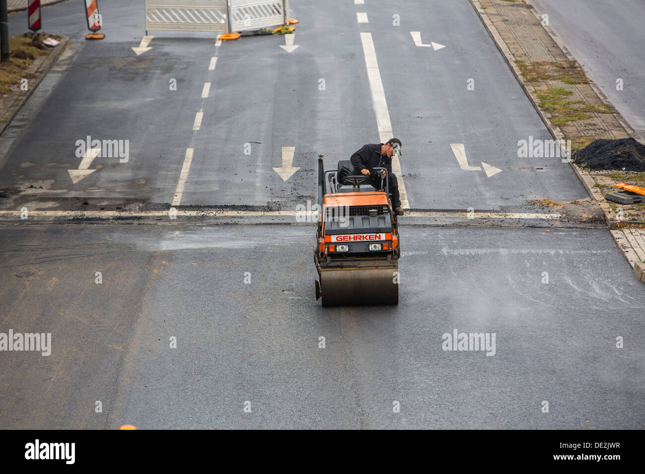Inner-city road construction site. Asphalted work on a major road junction. New asphalt surface. Alfred Street, Stock Photo