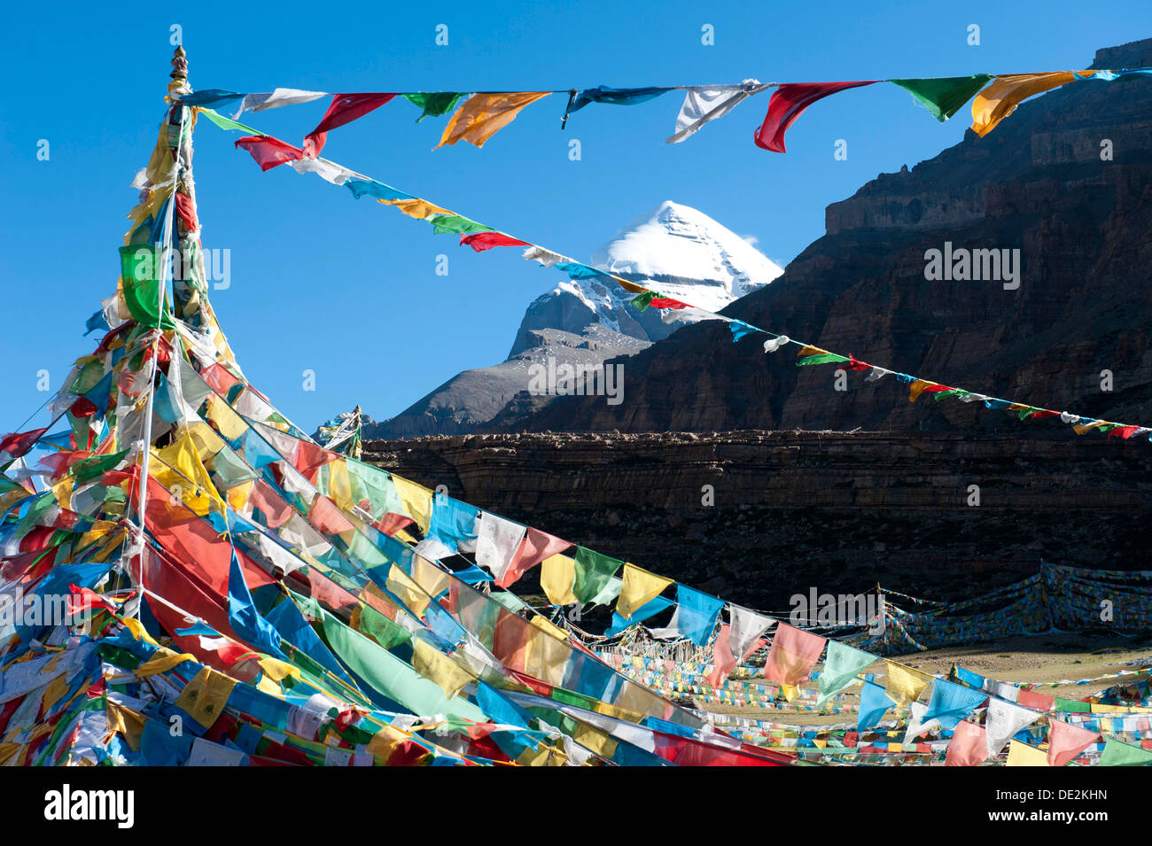 Tibetan Buddhism, Tarboche, a flagpole with colourful prayer flags, in front of the snow-covered holy Mount Kailash, south side - Stock Image