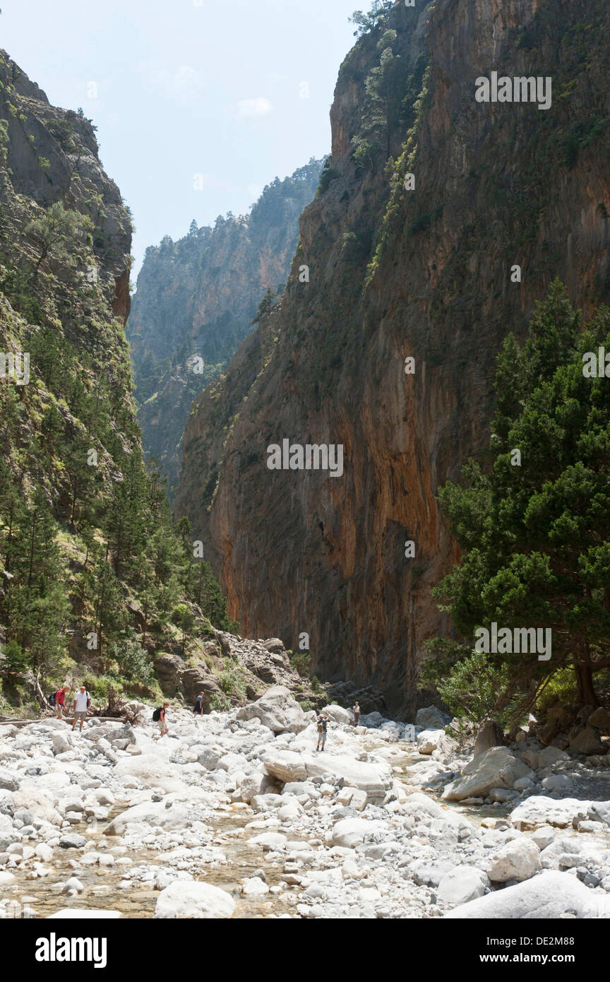 Steep cliffs rise up above the rocky bed of a stream, several hikers, 2nd Gate, view towards the south - Stock Image