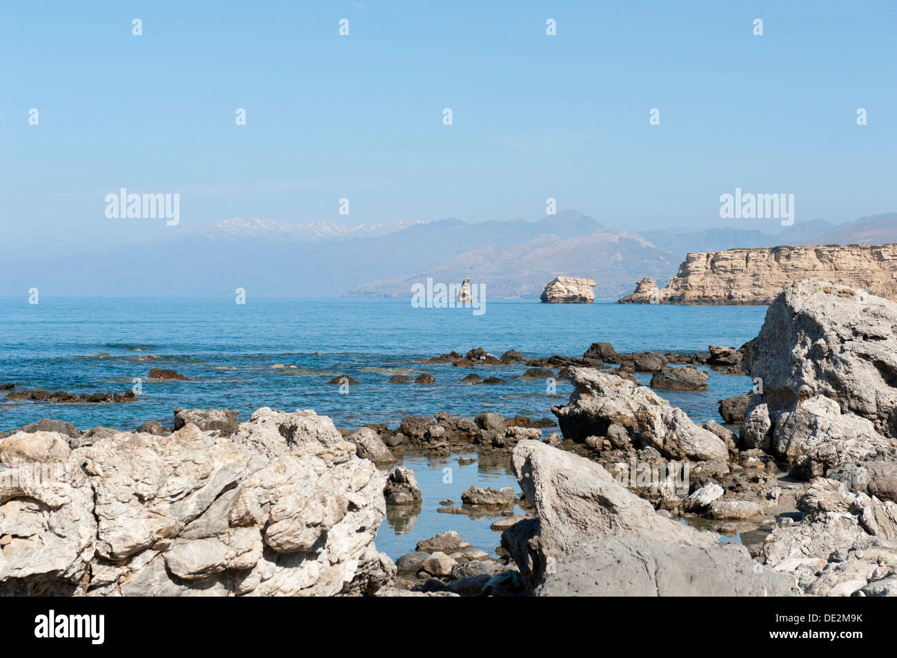 Secluded bay, coast, rugged limestone cliffs, Triopetra, Agios Pavlos, the White Mountains at back, Crete, Libyan Sea - Stock Image