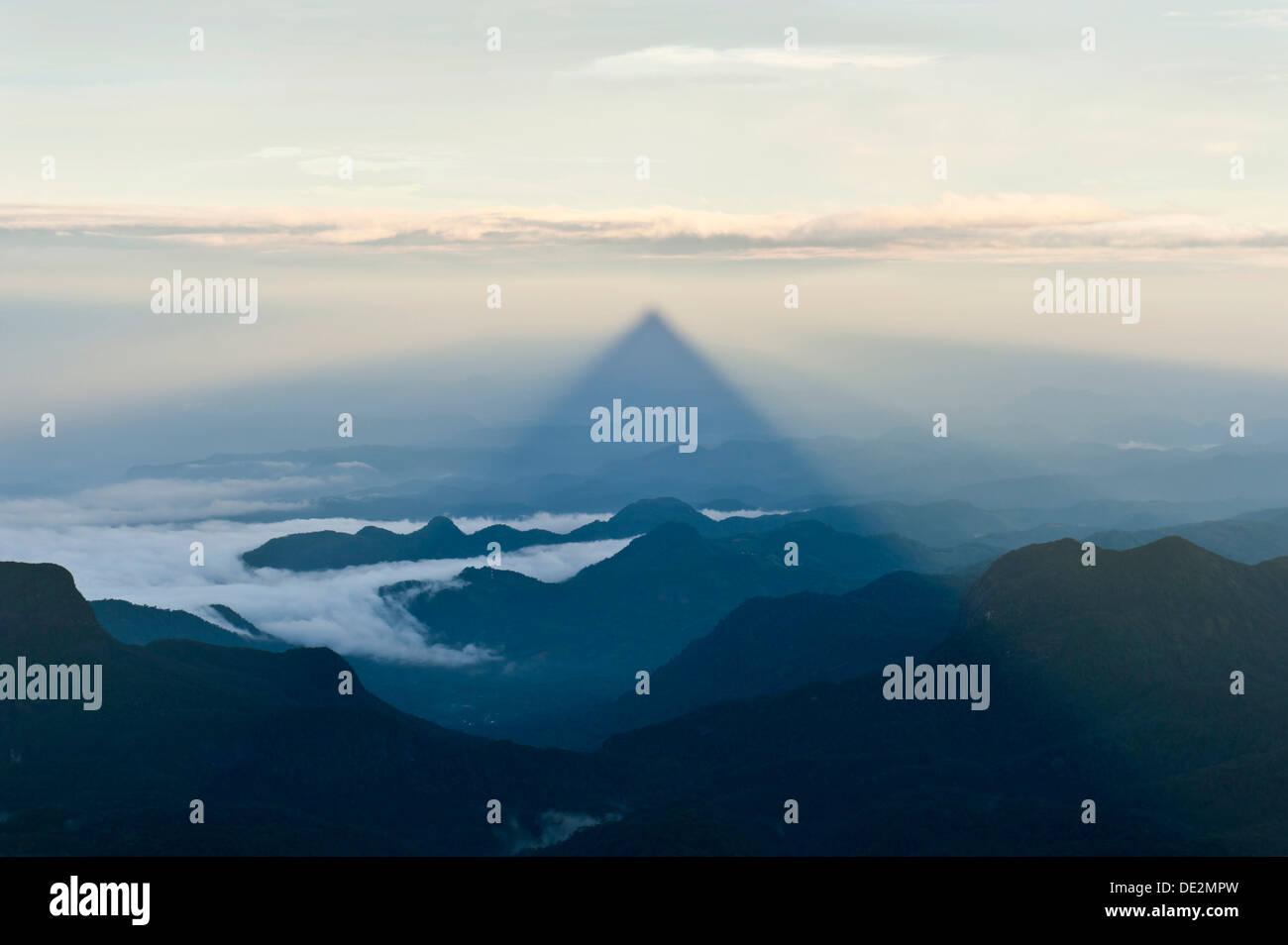 Pilgrim mountain, sun creating a triangle shadow in the landscape, image of God, Buddhist temple, Adam's Peak, Sri Pada - Stock Image