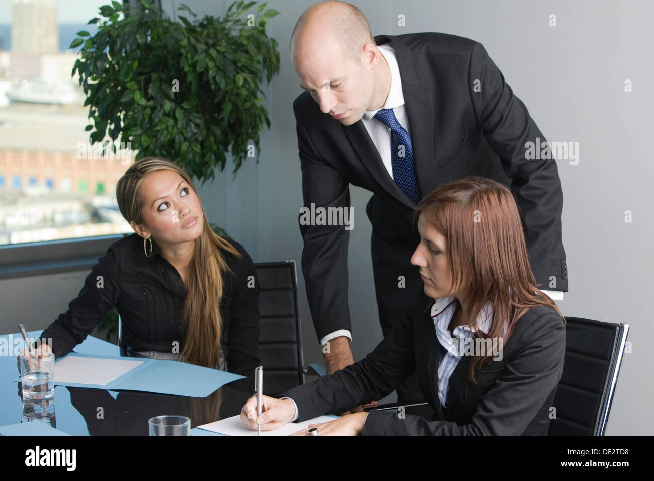 Consultation, three business people deliberating - Stock Image