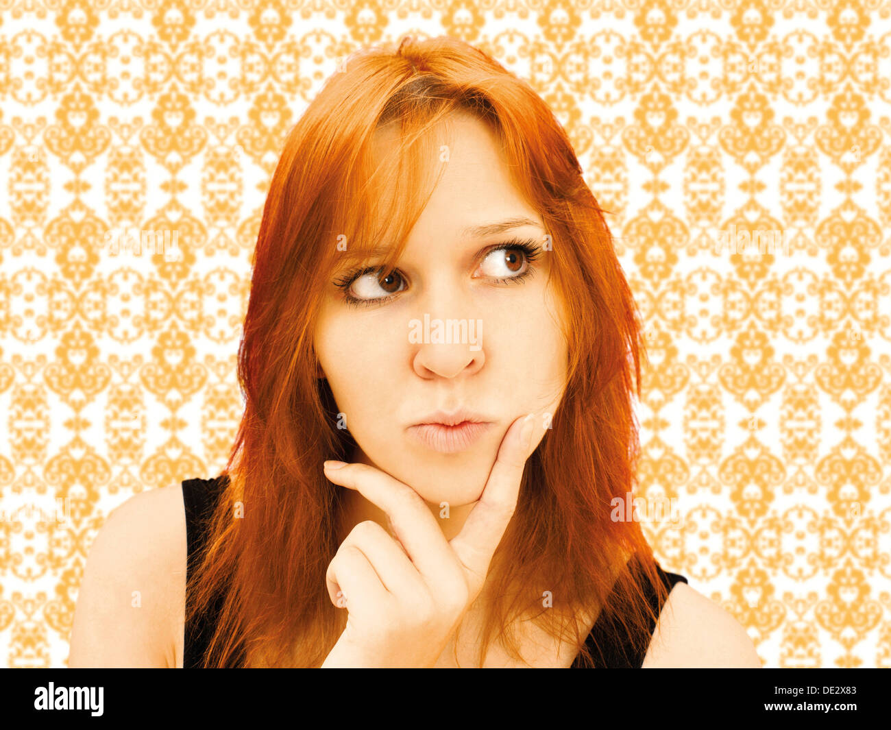 Portrait of a skeptical young woman in front of baroque wallpaper - Stock Image