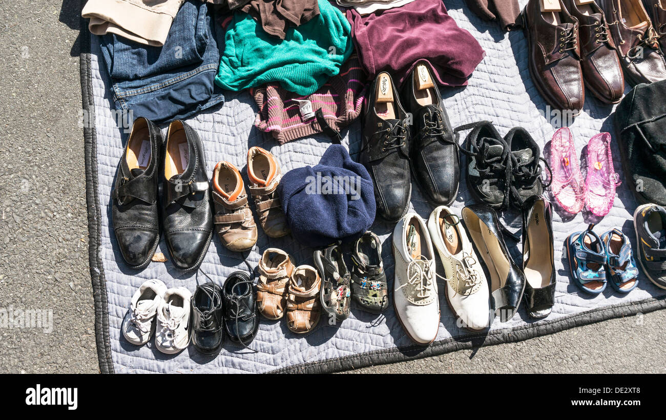 neat collection of shoes on suburban driveway at Edmonds garage sale suggest a story of one family's evolving growth & taste - Stock Image