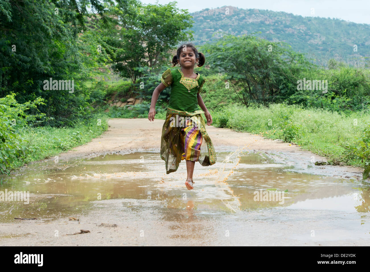 rural indian village girl running through a muddy puddle andhra