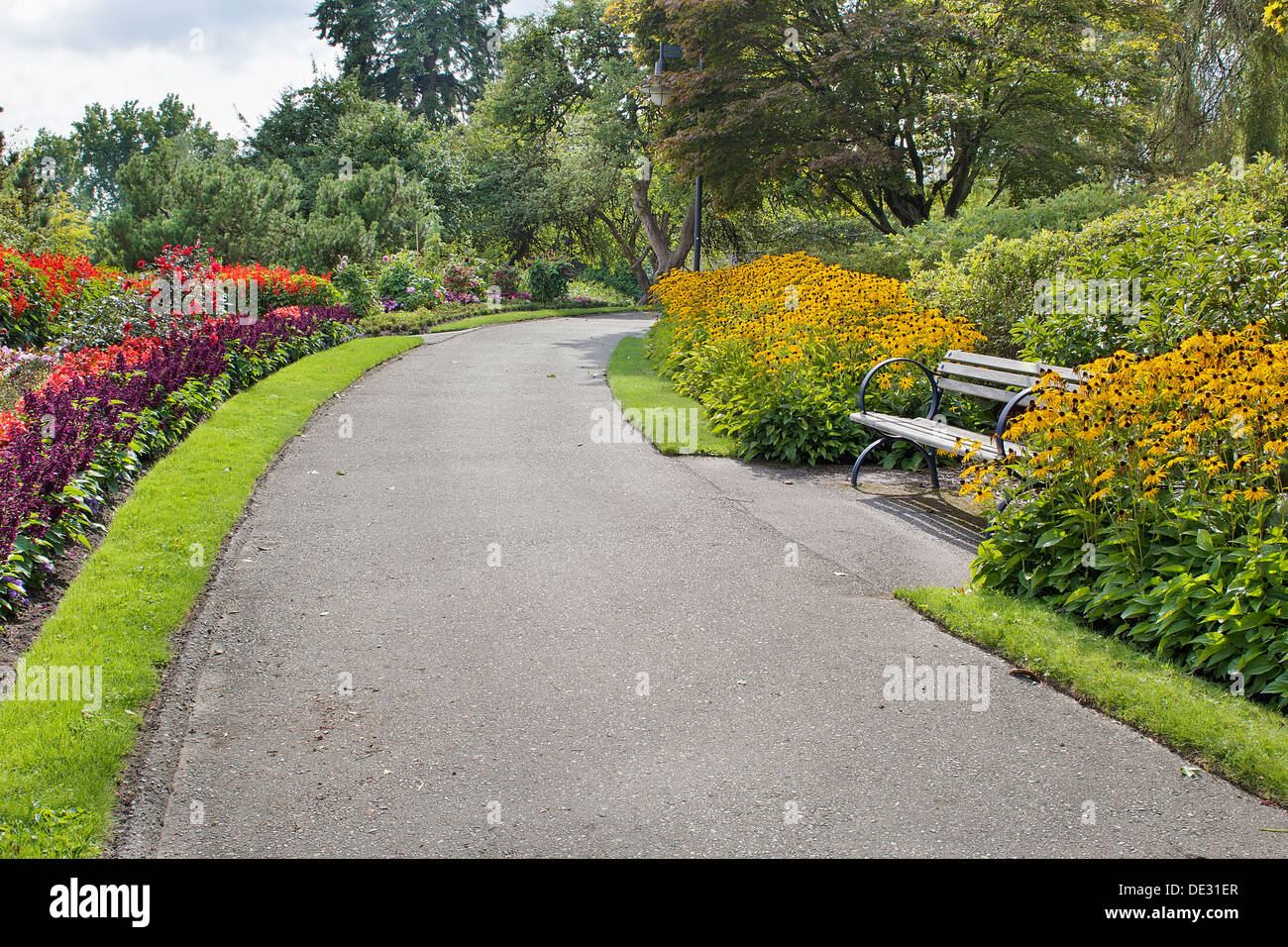 Neighborhood Public Parks Lined with Colorful Flowers Trees and Shrubs with Park Bench - Stock Image
