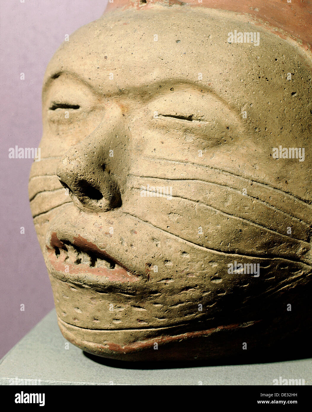 Pottery effigy-head vessel with sealed eyelids, stitched mouth and facial decorations. - Stock Image