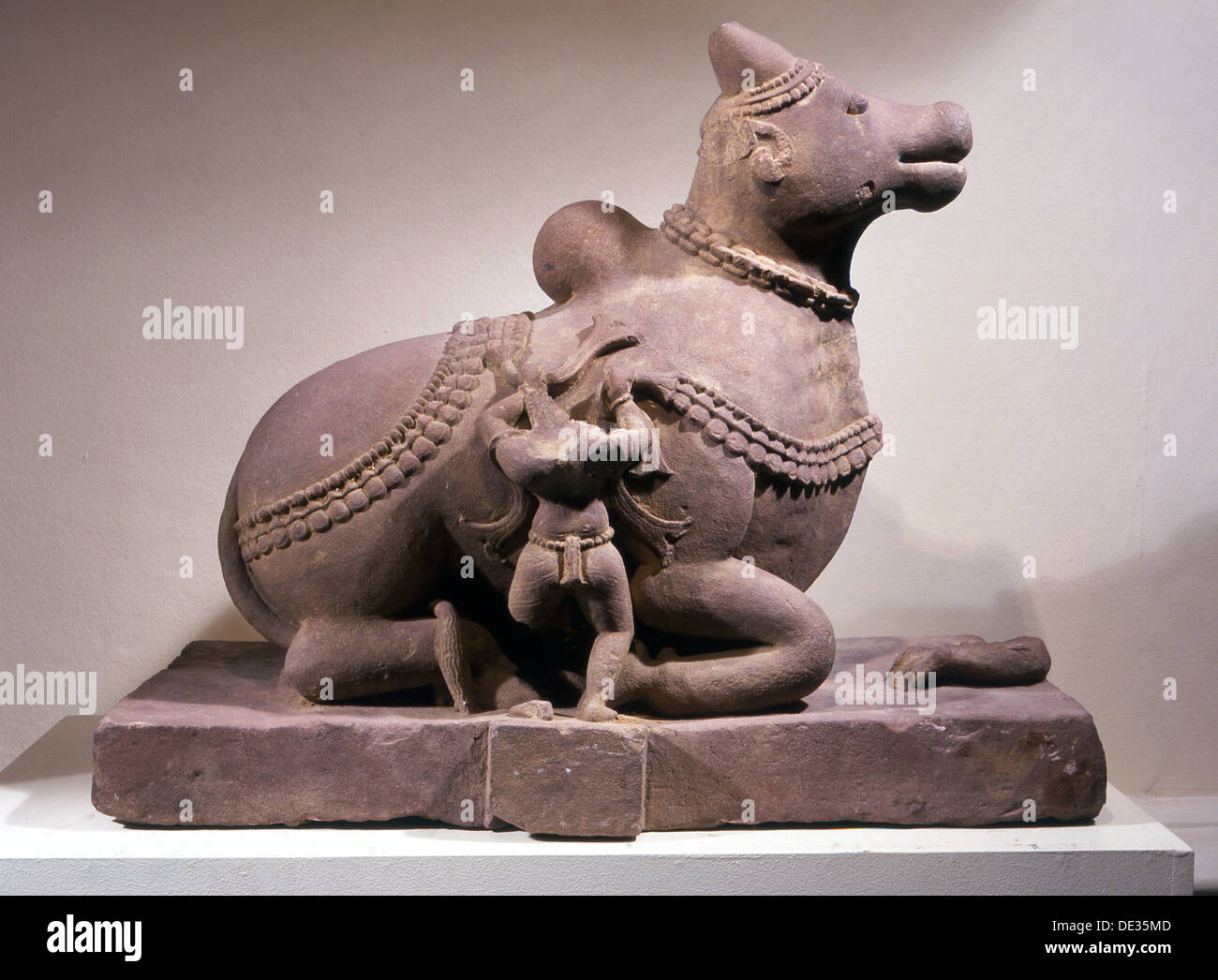 Free standing statue of Nandi, the bull mount of Shiva with attendant tying a garland around his neck. - Stock Image