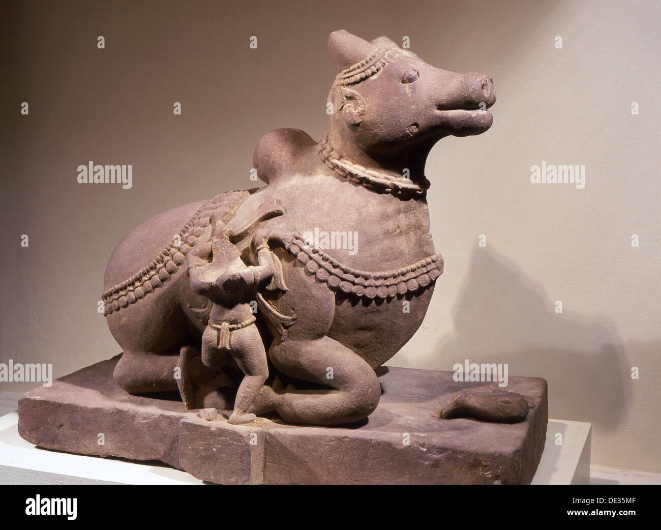 Free standing statue of Nandi, the bull mount of Shiva, with attendant tying a garland around his neck. - Stock Image