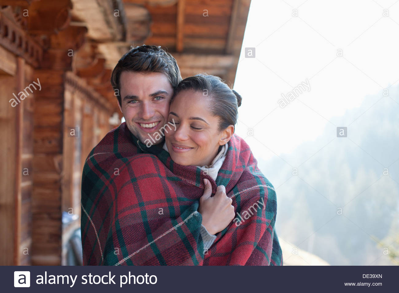 Portrait of smiling couple wrapped in a blanket on cabin porch - Stock Image