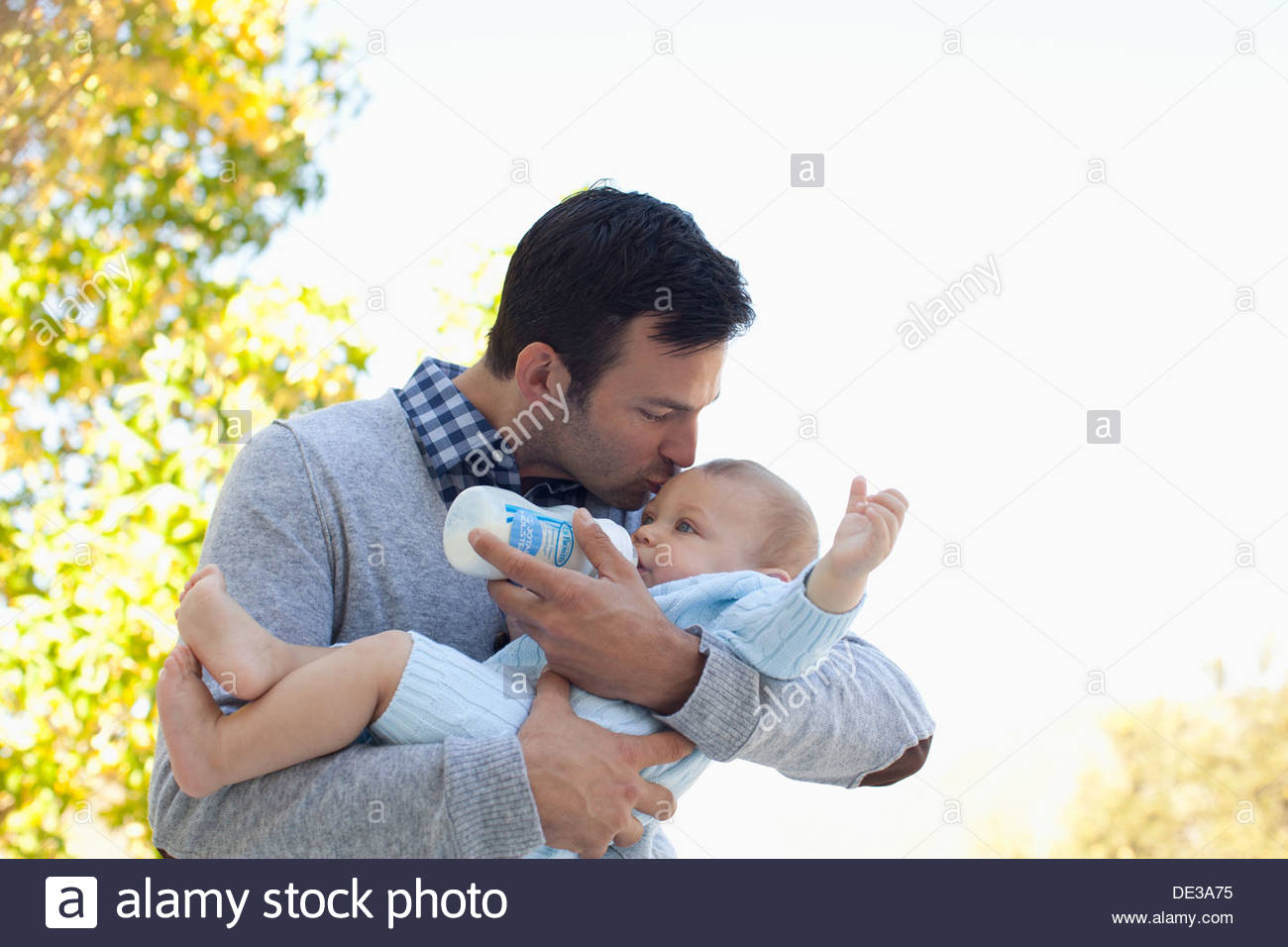 Father bottle feeding baby outdoors - Stock Image