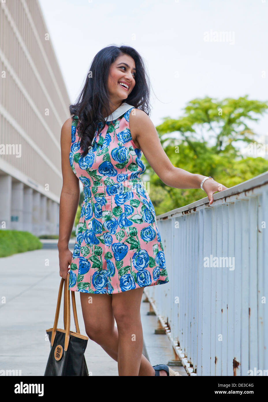 Young woman in urban environment wearing floral pattern one-piece dress - Stock Image