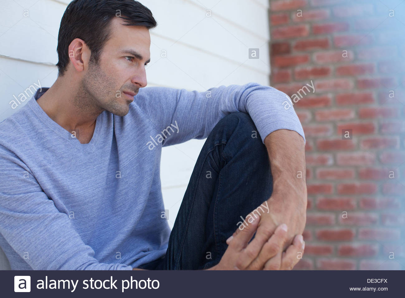 Man with hands clasped - Stock Image