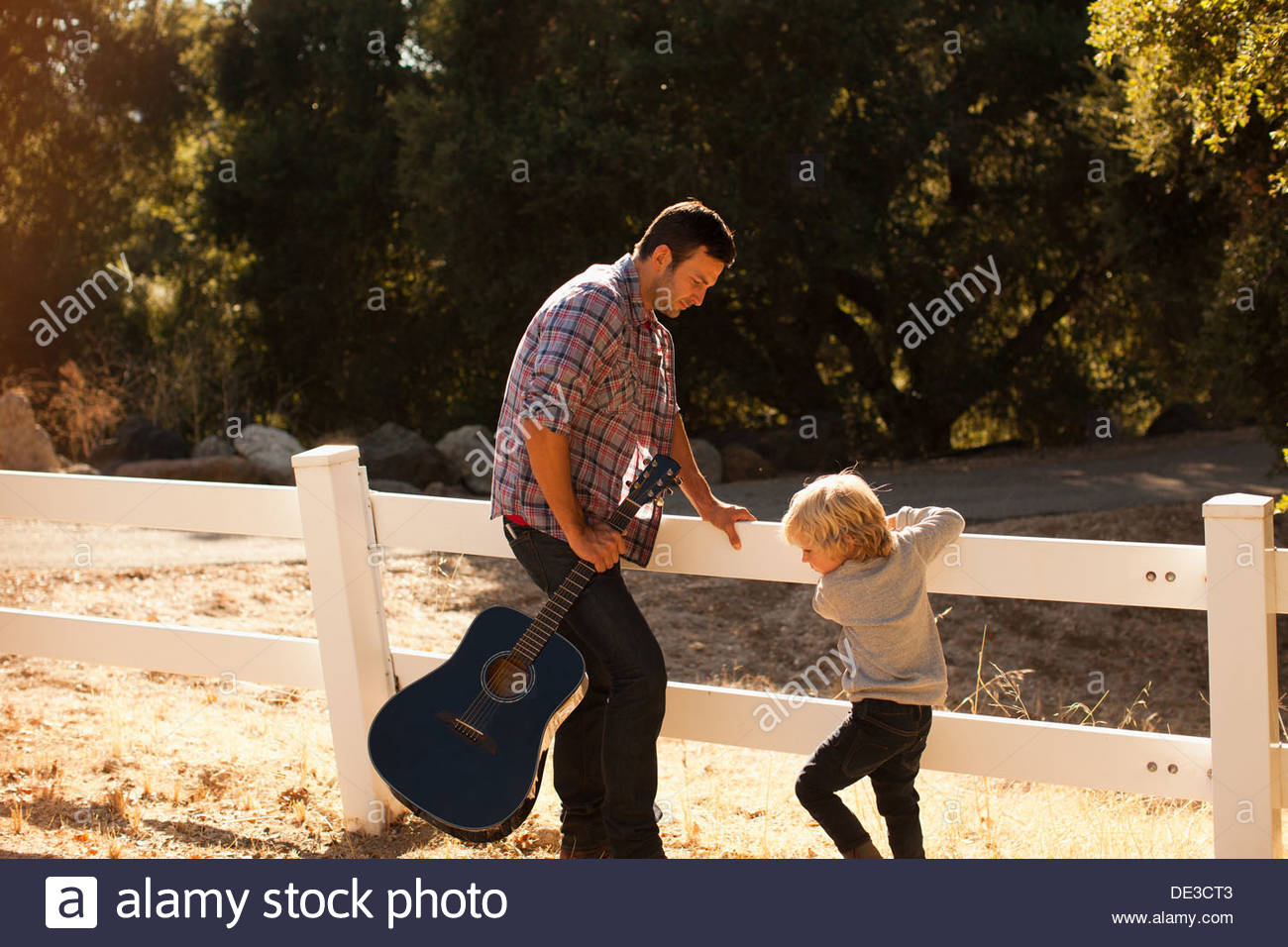Father and son playing in dirt road - Stock Image
