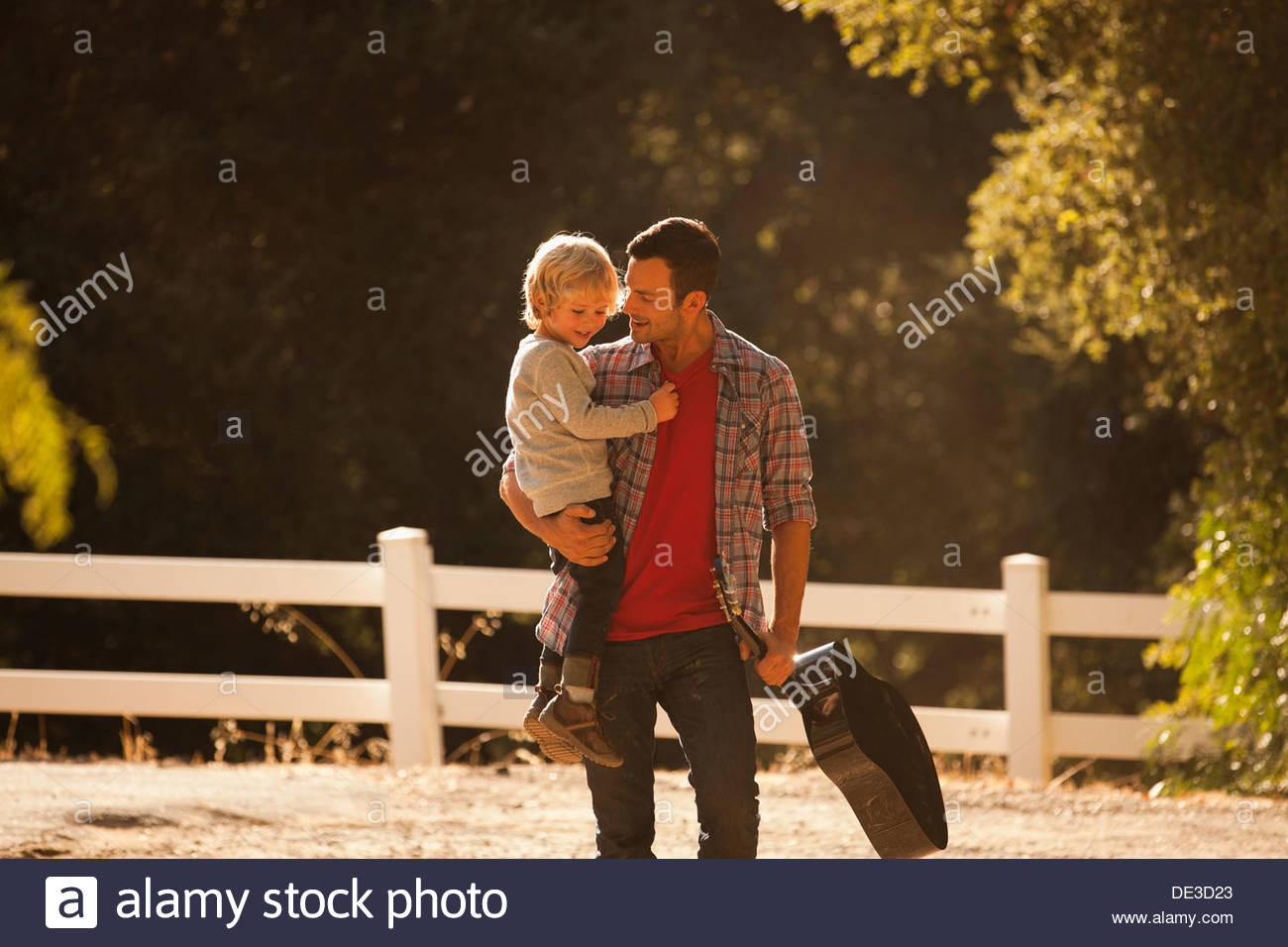 Father carrying son and guitar on dirt road - Stock Image
