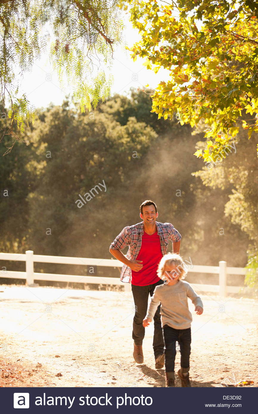 Father chasing son on dirt road - Stock Image