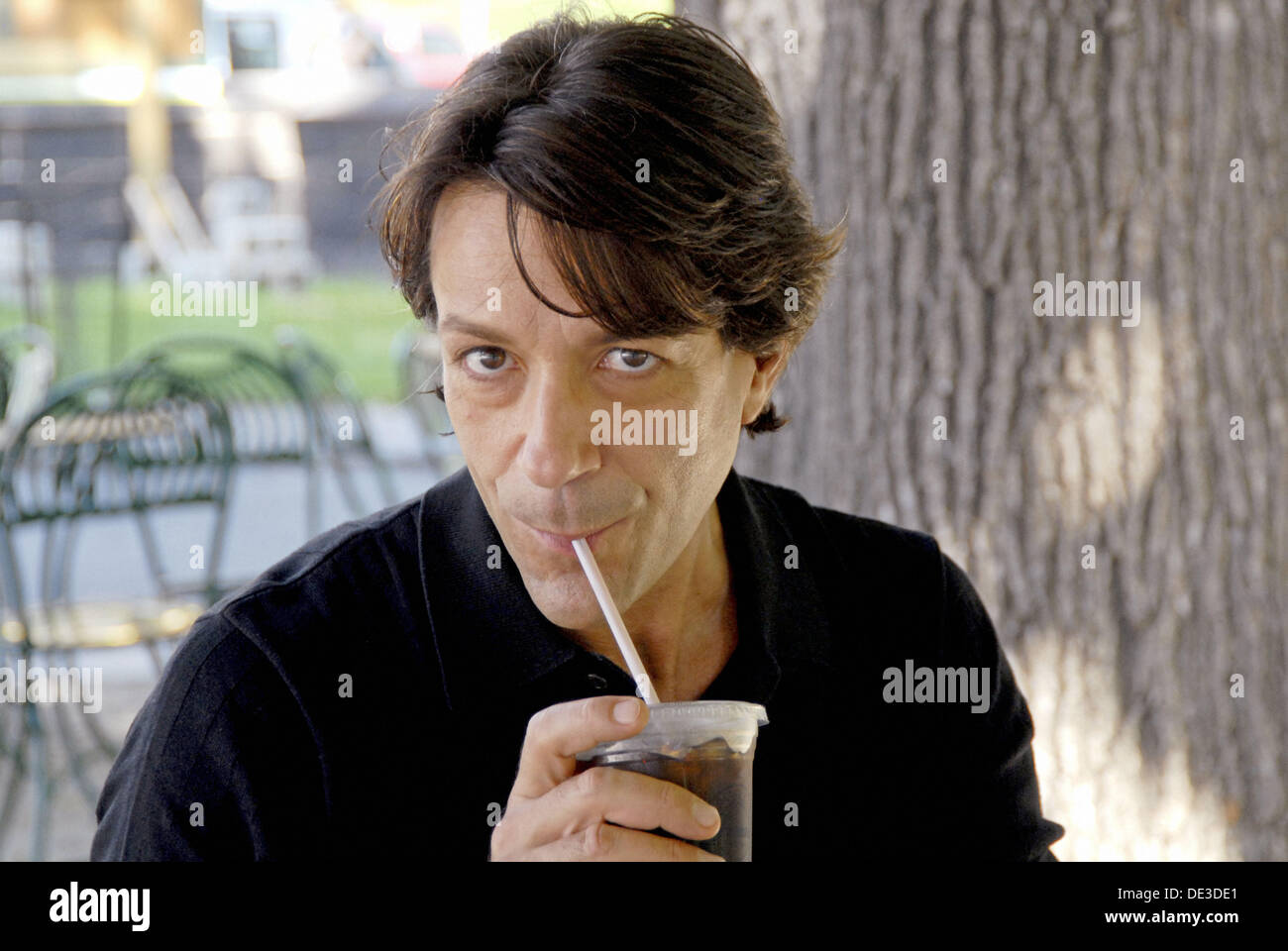 40-45 year old caucasian male, sipping iced coffee, at an outdoor café - Stock Image
