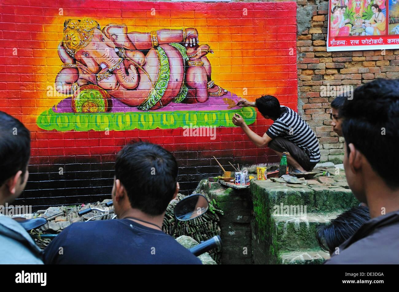 Man panting sleeping Ganesh on the wall on the street - Stock Image