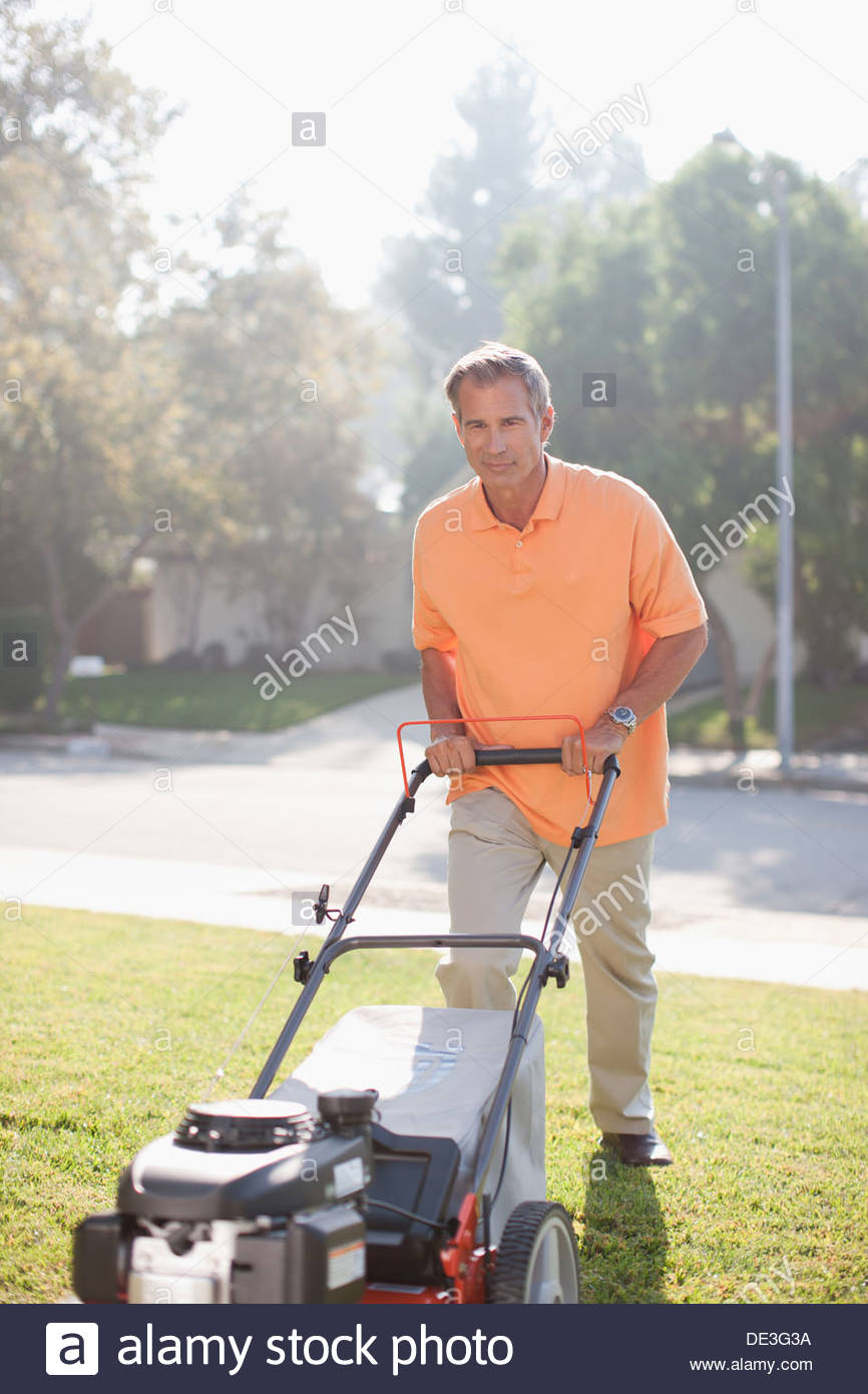 Older man mowing front lawn - Stock Image