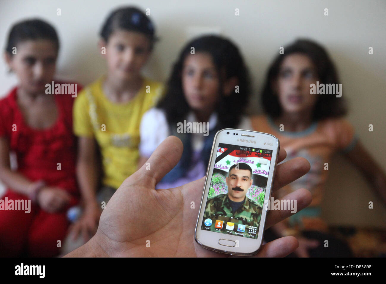 On the screen of a smarthphone the photo of a fallen soldier of the Syrian Arab Army killed by rebels is displayed in Damaskus, Syria on September 19, 2013. In the background the children of the killed soldier, which are displaced from Aleppo, are seen. Photo: Martin Lejeune - Stock Image