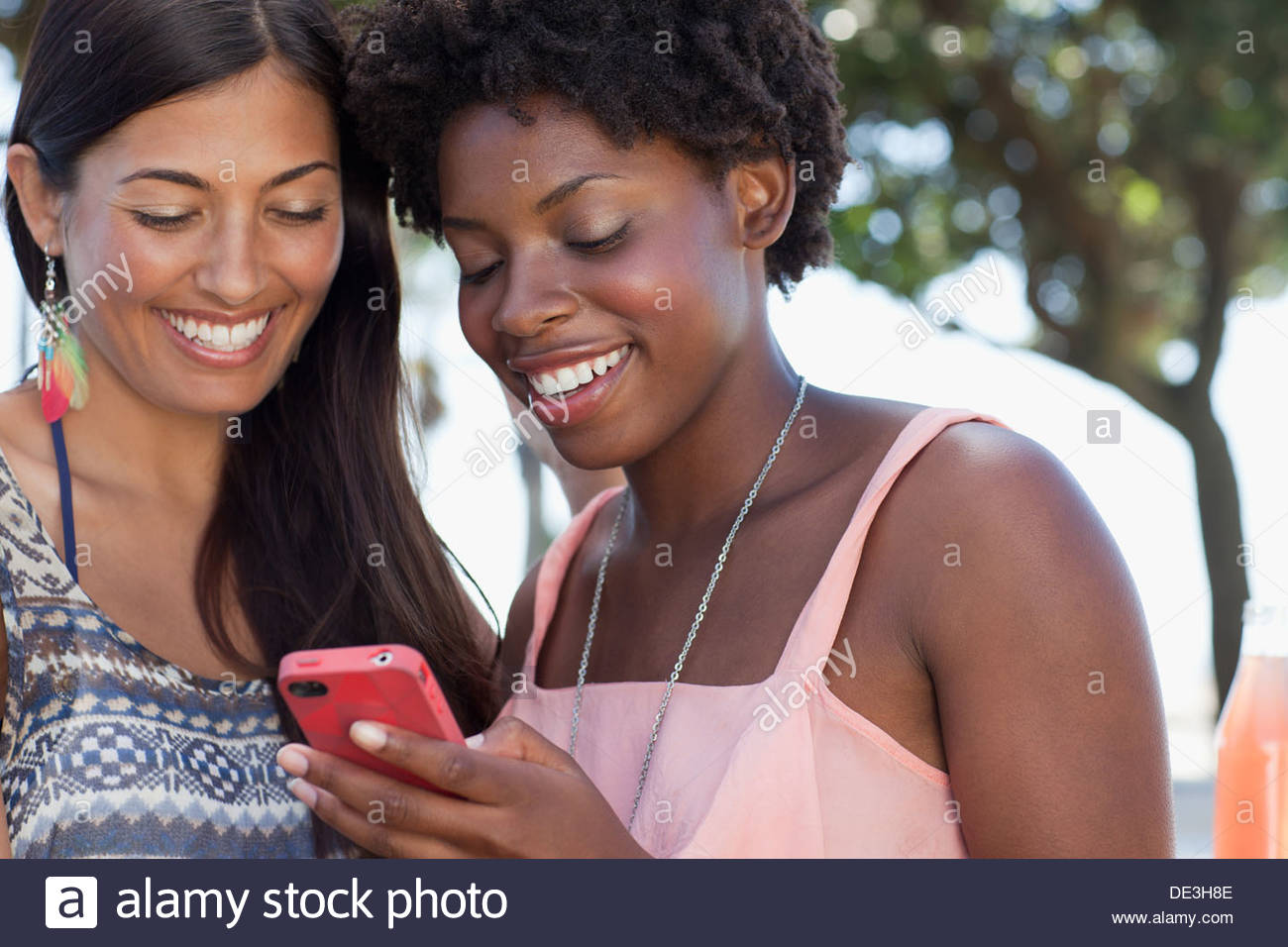 Women using cell phone together - Stock Image