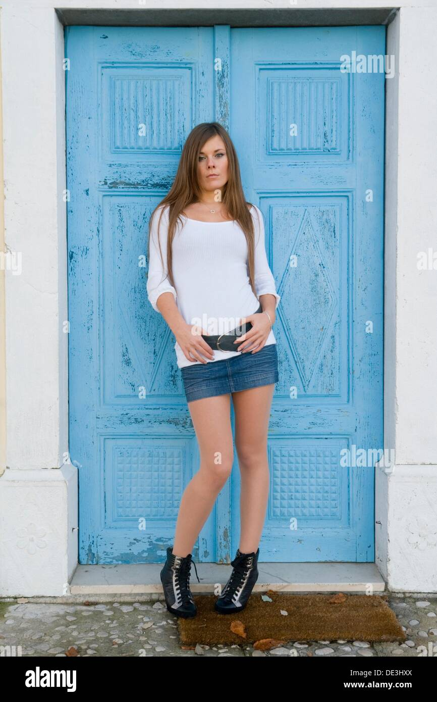 Posing pretty young woman in front of bright Blue wooden doors - Stock Image