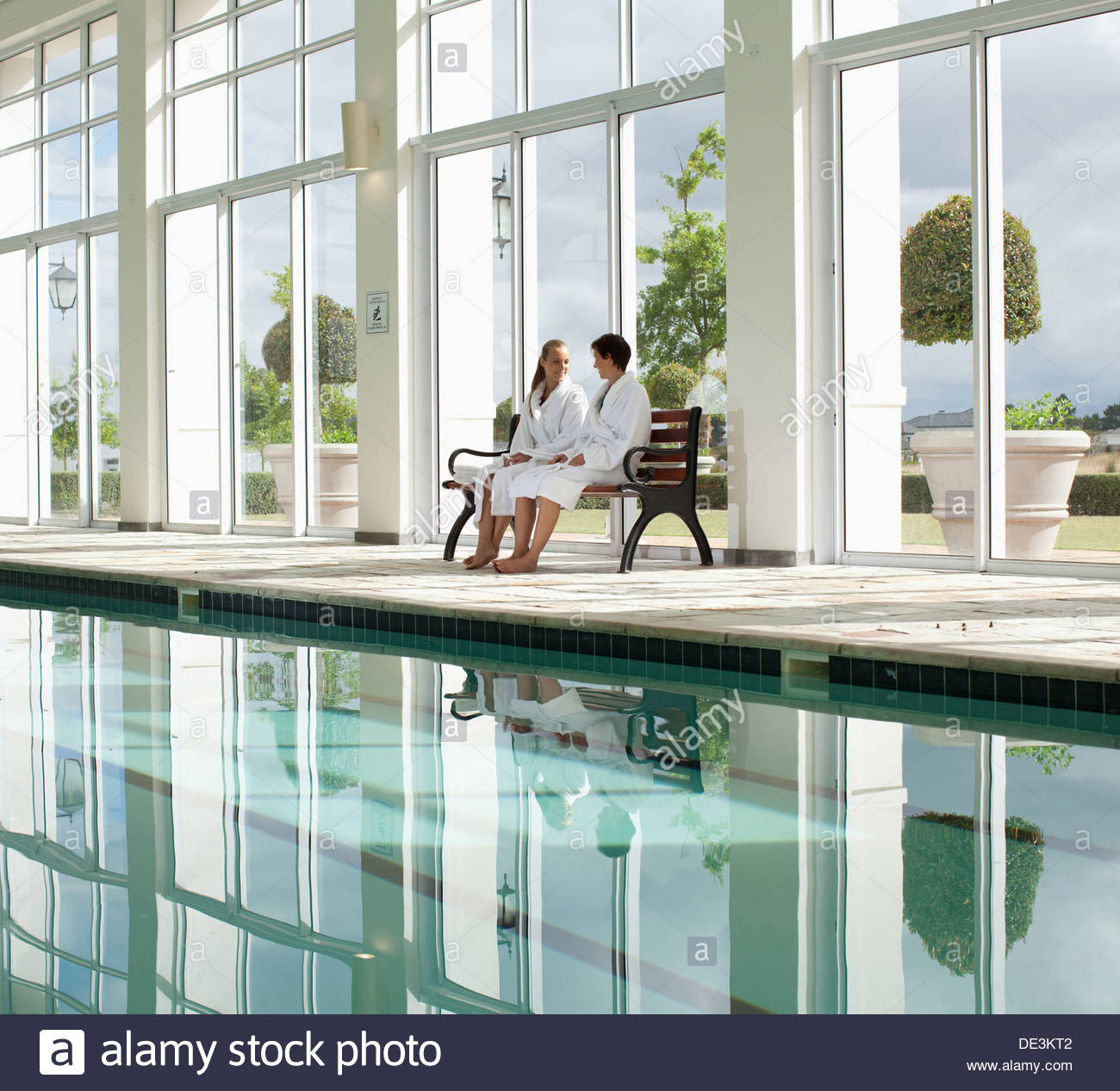 Two women sitting beside swimming pool - Stock Image