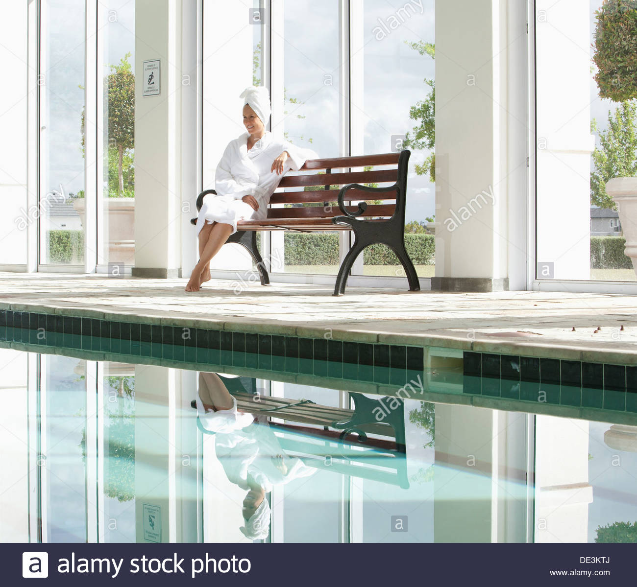 Portrait of smiling woman in bathrobe sitting on bench poolside at spa Stock Photo
