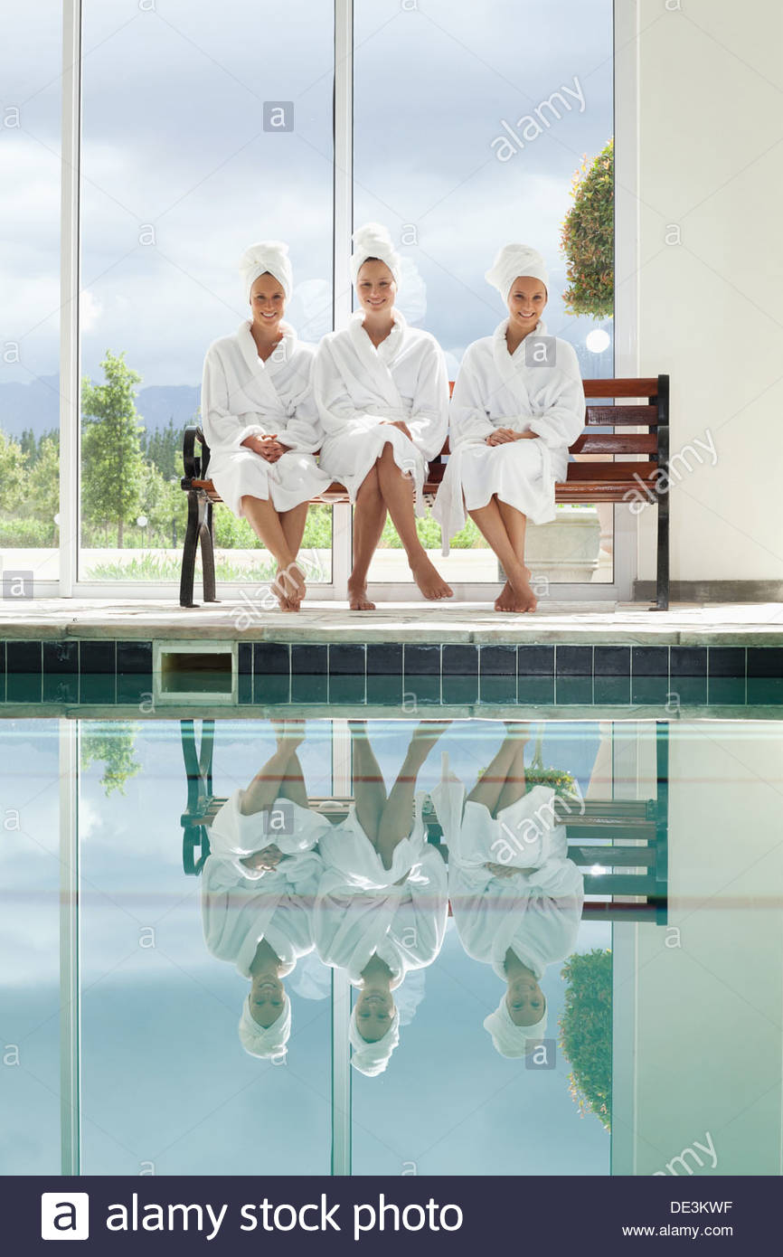 Women in bathrobes talking on bench poolside at spa Stock Photo