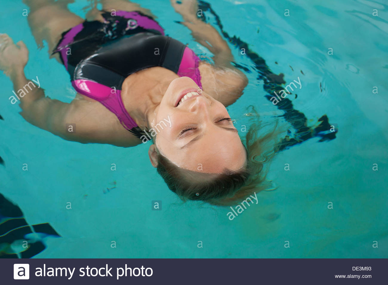 Close up of smiling woman floating on back in swimming pool - Stock Image