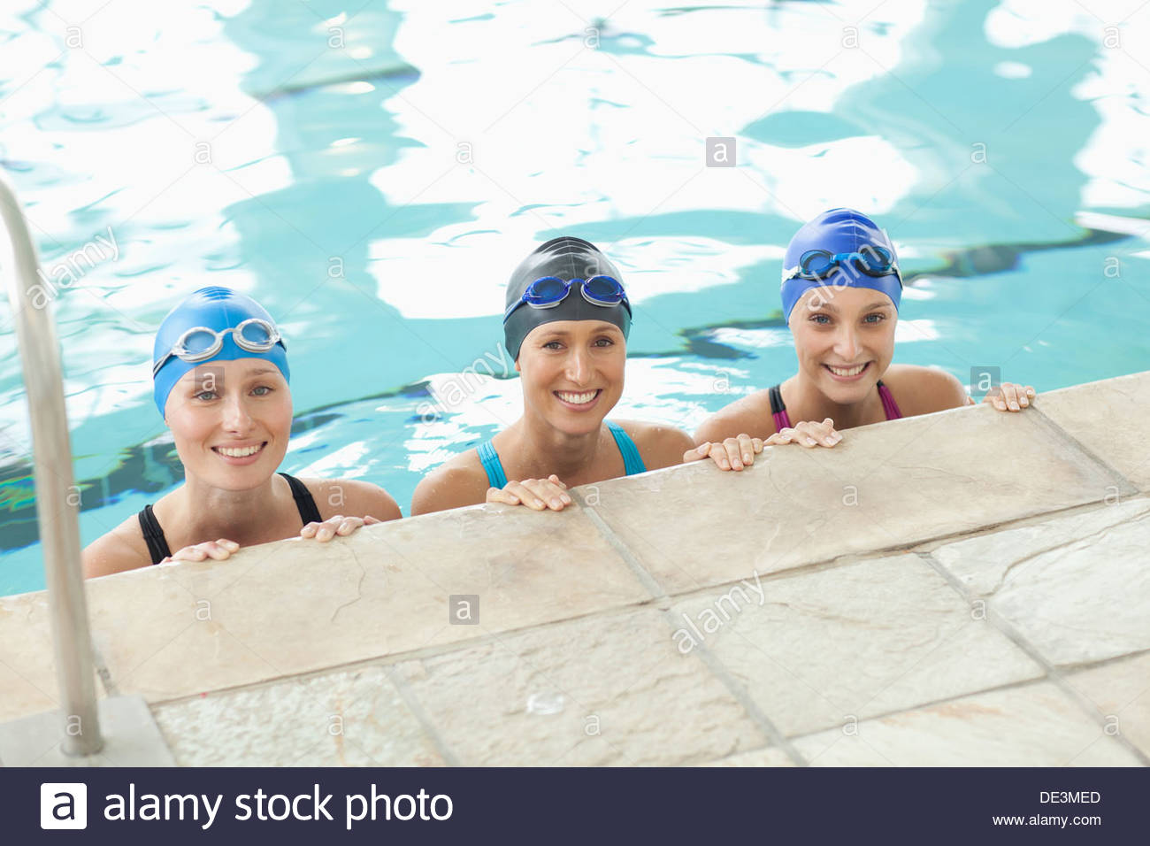Portrait of smiling women at edge of swimming pool - Stock Image