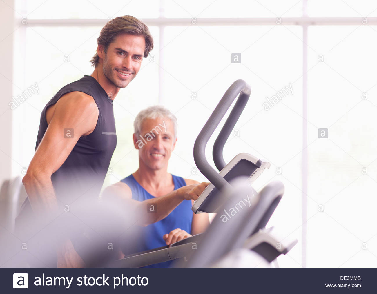 Men talking on treadmill in gymnasium - Stock Image