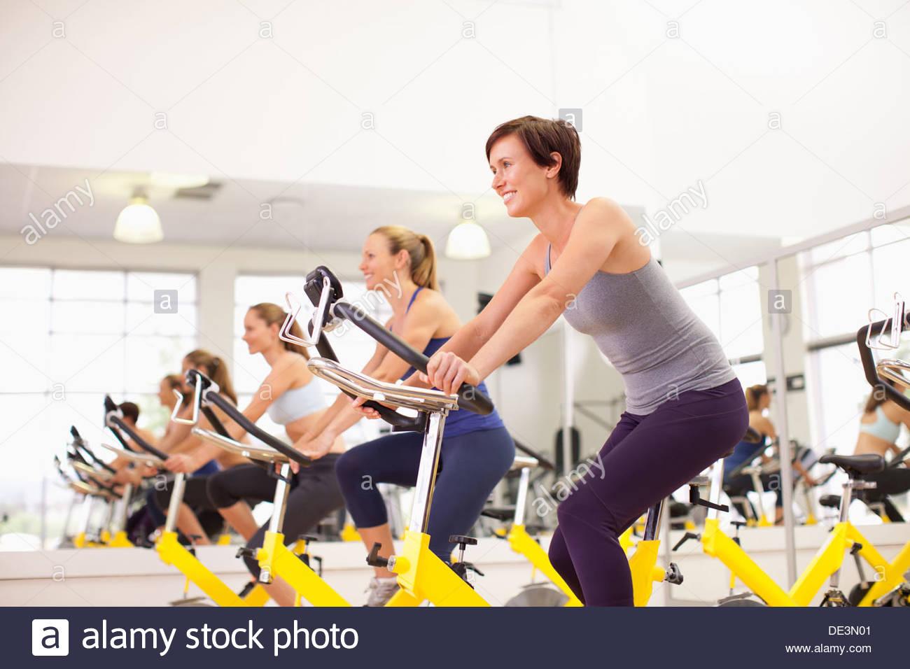 Portrait of smiling women on exercise bikes in gymnasium - Stock Image