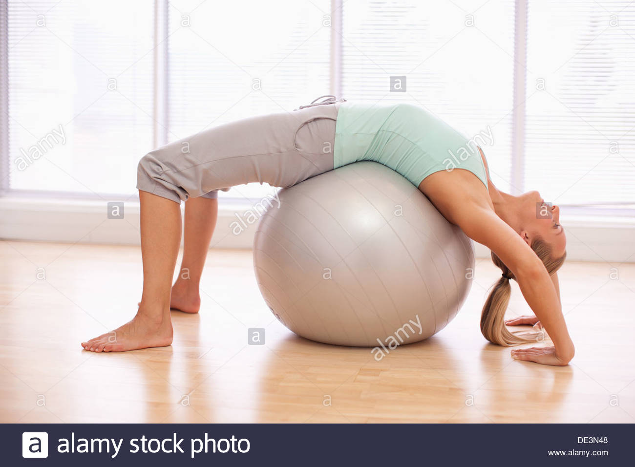Woman doing sit-ups with fitness ball - Stock Image