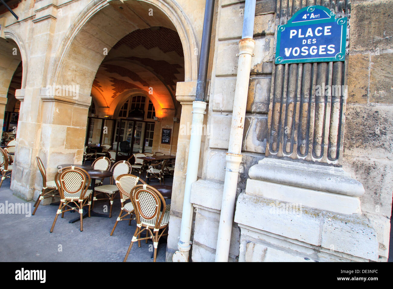 The Marais, Place de Vosges - coffee house sheltered under arches with it's wicker chairs and circular tables, Paris, France - Stock Image